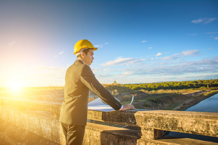 Engineer standing against landscape