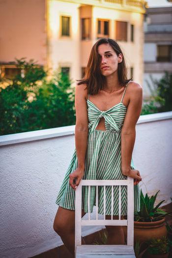 Beautiful young woman standing in balcony