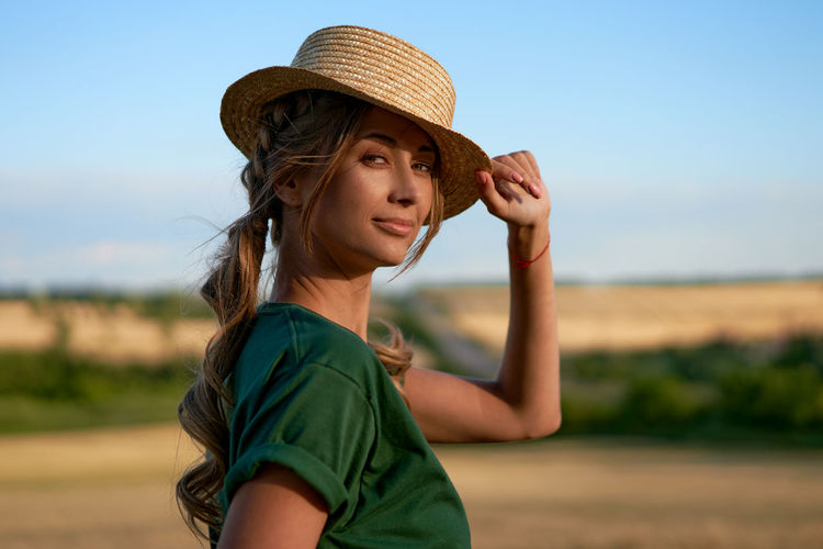 Portrait of young woman wearing hat against sky