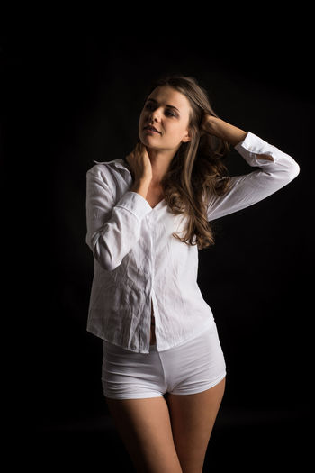 One Person Black Background Three Quarter Length Studio Shot Young Adult Hairstyle Hair Women Long Hair Front View Beautiful Woman Indoors  Young Women Standing Beauty Casual Clothing Adult Portrait Arms Raised Human Arm Contemplation Human Limb