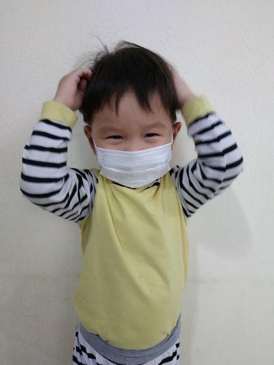 Cute boy standing against wall