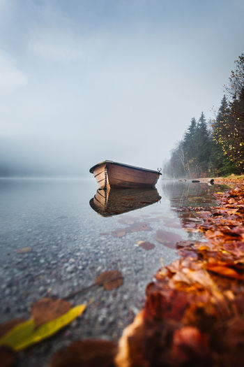 Water Sky Nature Tranquility Beauty In Nature Day Scenics - Nature Reflection Tranquil Scene Plant No People Lake Tree Non-urban Scene Outdoors Solid Rock Floating On Water Surface Level Nautical Vessel Boat Fall Beauty Fall Colors Fog Reflection