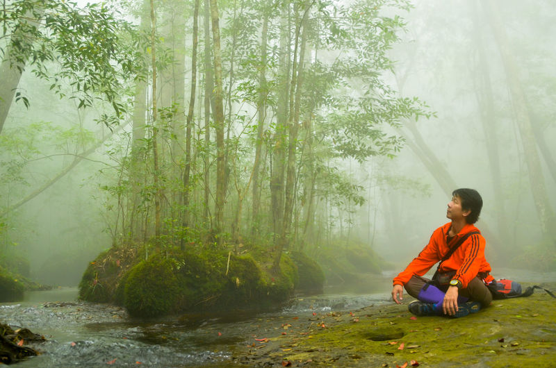 Full Length Of Man Meditating While Sitting In Forest