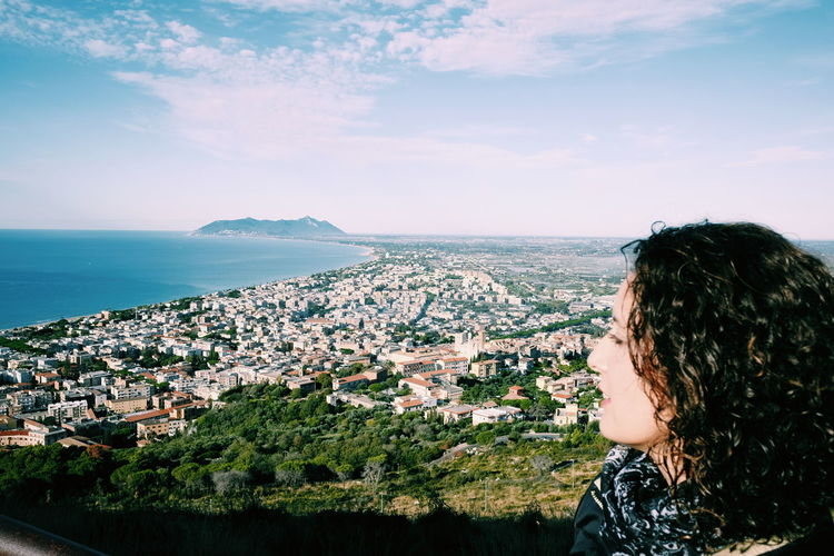 Mid adult woman looking at view while standing on mountain against sky