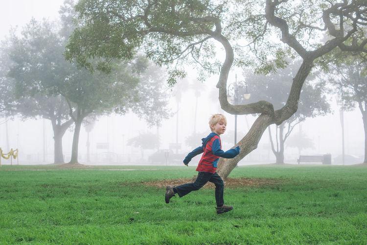 Full length of boy running against tree at park