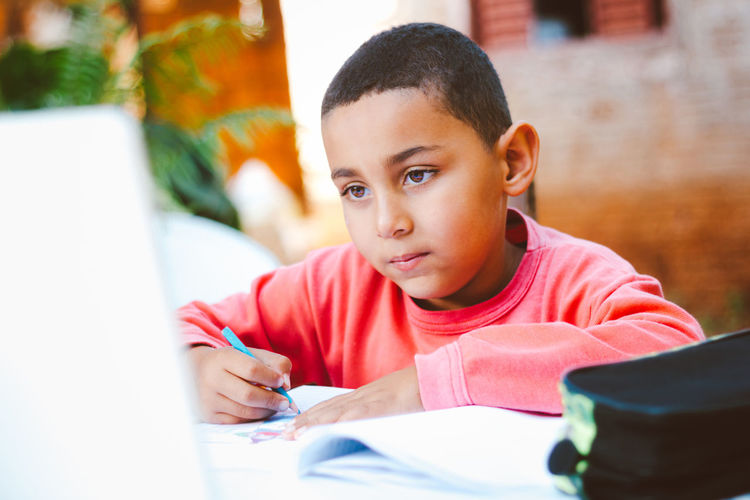 Boy looking away while sitting on table