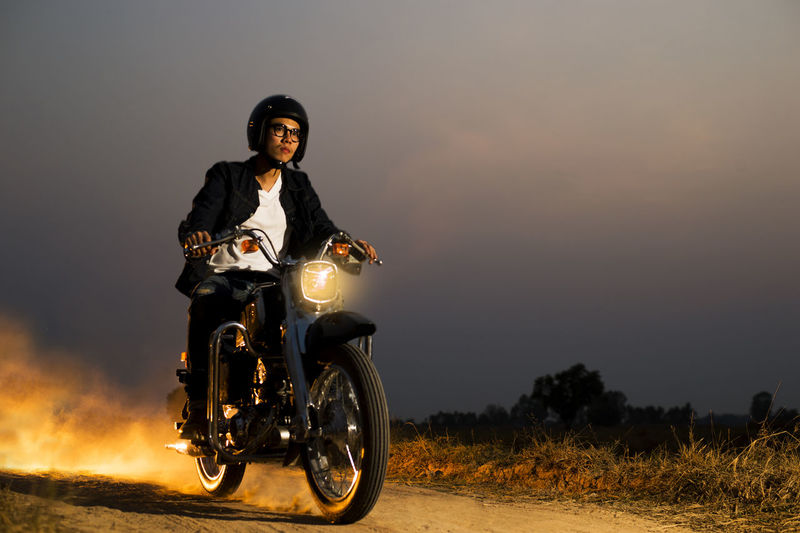 Young man riding motorcycle on road