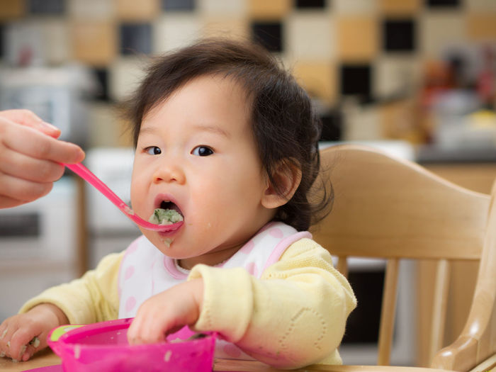 Close-up portrait of cute baby girl eating food at home