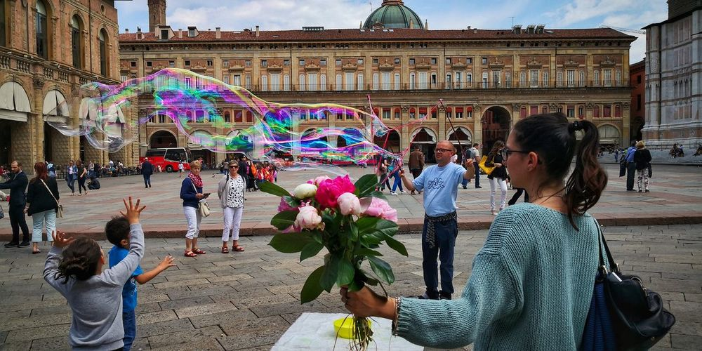 Shooting day Flower Project Potography Bologna, Italy EyeEm Best Shots Springtime Posing For The Camera Bubbles Flowers Peonias City Multi Colored Flower Men Women History Architecture Sky Building Exterior Built Structure Bubble Wand Blowing Soap Sud Holi Town Square Crowd Crowded 2018 In One Photograph