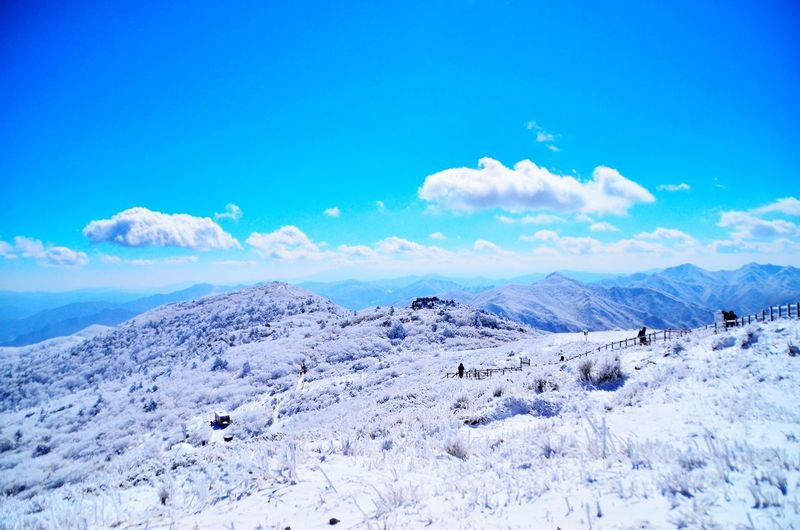 Scenic view of mountain range against blue sky