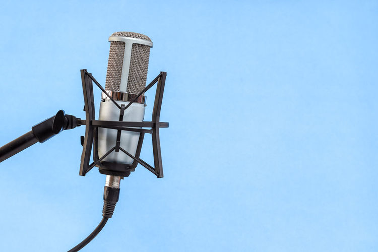 Microphone on blue background Sky Blue Low Angle View Clear Sky Metal No People Nature Day Copy Space Lighting Equipment Technology Outdoors Sunlight Electricity  Protection Street Light Built Structure Light Security Architecture Electrical Equipment Electric Lamp Power Supply