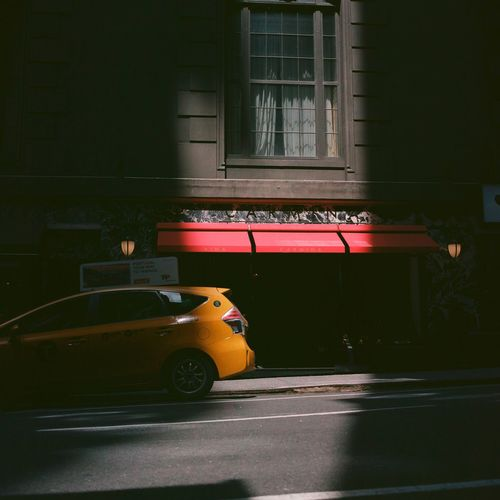 Yellow car on road by buildings in city