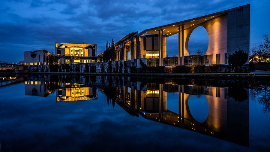 German Chancellery Building Reflection In Spree River Against Sky At Night
