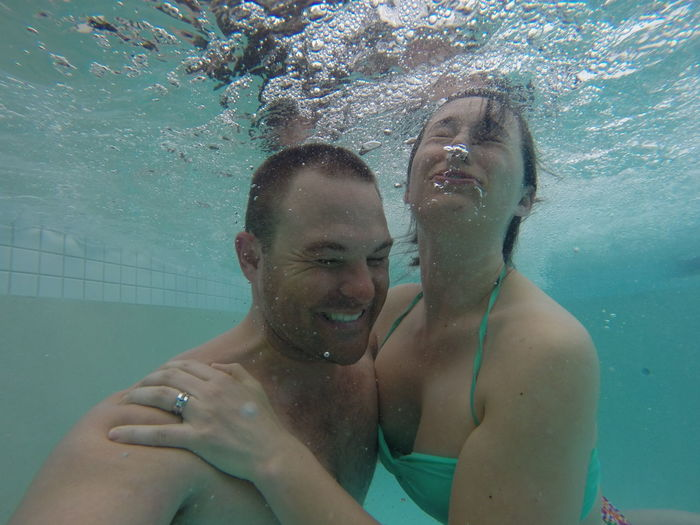 Happy Couple Swimming In Pool
