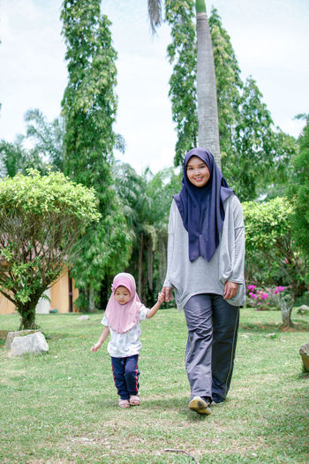 Full length of mother and daughter against trees