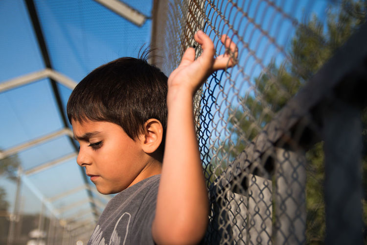 Little boy against chainlink fence