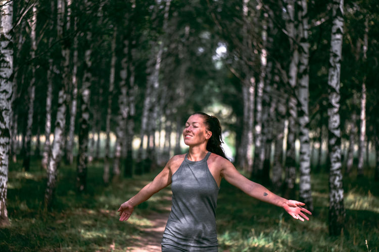 Happy woman standing on field against trees in forest