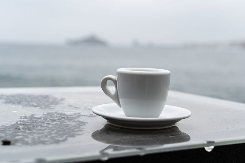 A coffe alone at Capo Mulini (Acireale CT) Cup Drink Mug Food And Drink Crockery Coffee Cup Coffee - Drink Water Table Outdoors Day No People Focus On Foreground Hot Drink Refreshment Coffee Nature Sea Faraglioni Acitrezza  Capo Mulini Acireale Sicily Seaside Seascape Espresso Loneliness Sadness Rainy Day Rain