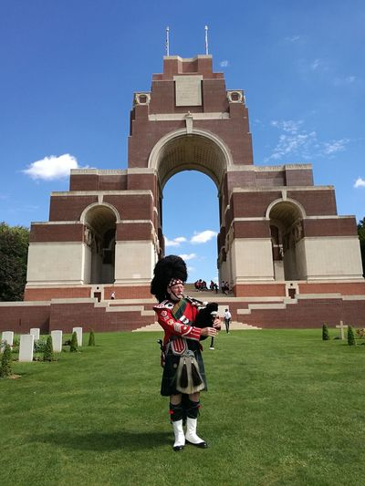 Senior Man Playing Bagpipe At Cemetery