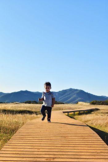 Girl walking on boardwalk against clear sky