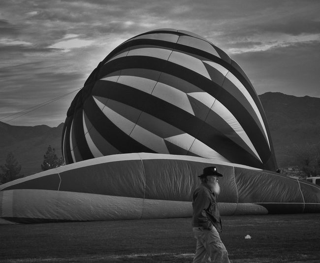 Side view of mature man with hands in pockets walking by hot air balloon on field