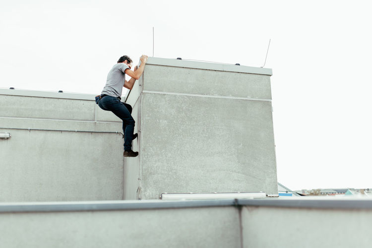 Low angle view of man climbing on building against clear sky