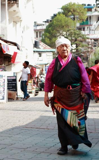 Full length portrait of man walking on street in city