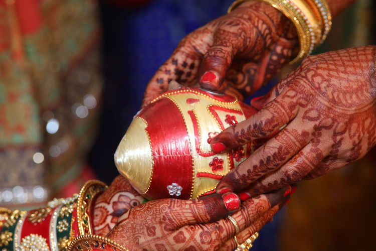Cropped hands of women during traditional ceremony