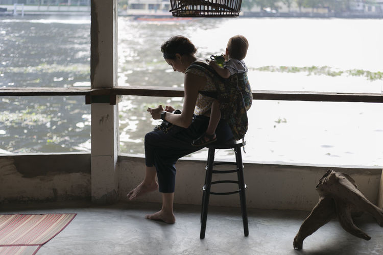 Two People Full Length Real People Men Sitting Seat Togetherness Bonding Casual Clothing Young Adult Adult Window People Lifestyles Water Leisure Activity Males  Day Women Positive Emotion Shorts Couple - Relationship
