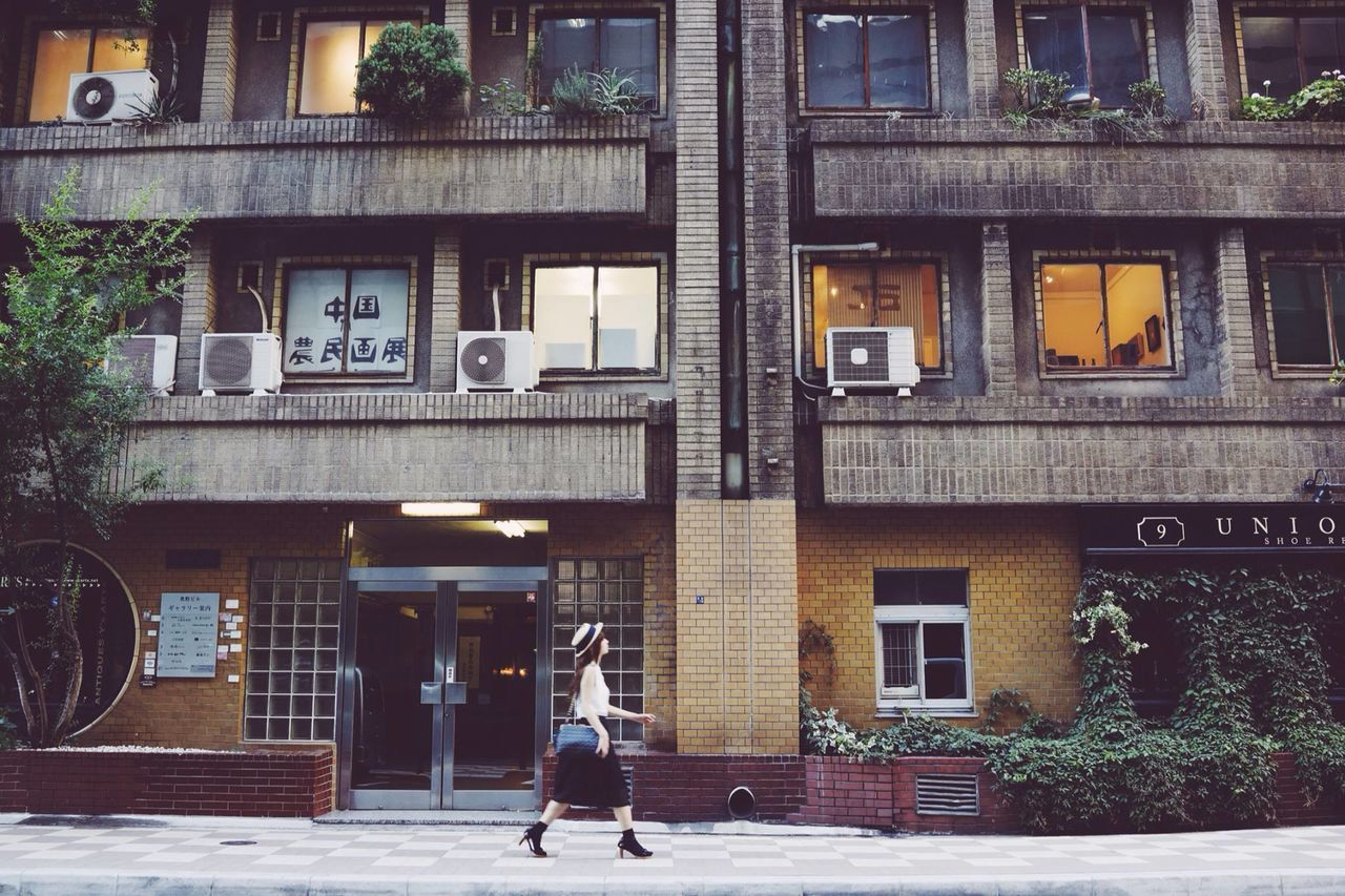 Side view of young woman walking in front of buildings