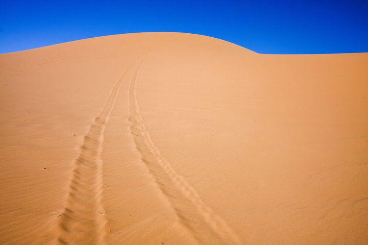 Sand dunes in desert against clear sky