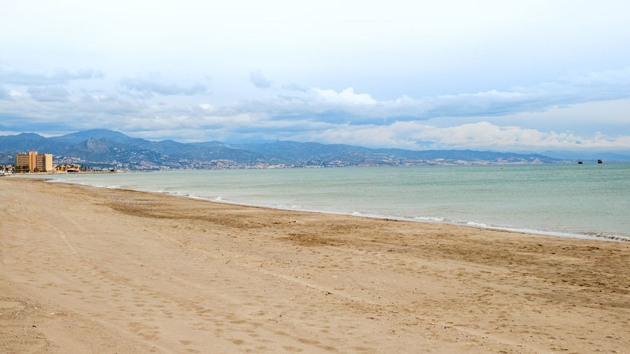 empty beach with dark clouds Empty Beach With Dark Clouds Beach Photography Water Land Beach Sky Sea Sand Cloud - Sky Beauty In Nature Mountain Scenics - Nature Tranquil Scene Tranquility Nature Day Outdoors No People Travel Non-urban Scene Place