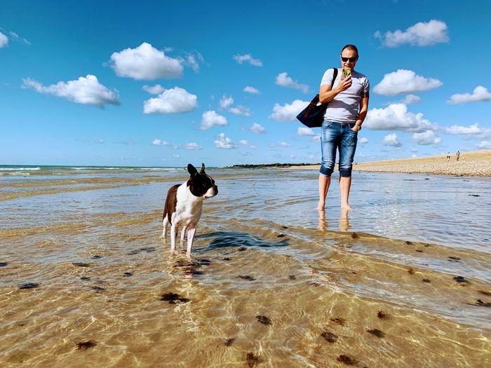 Full length of woman standing on beach against sky
