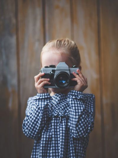 Close-up of girl photographing with camera against wall