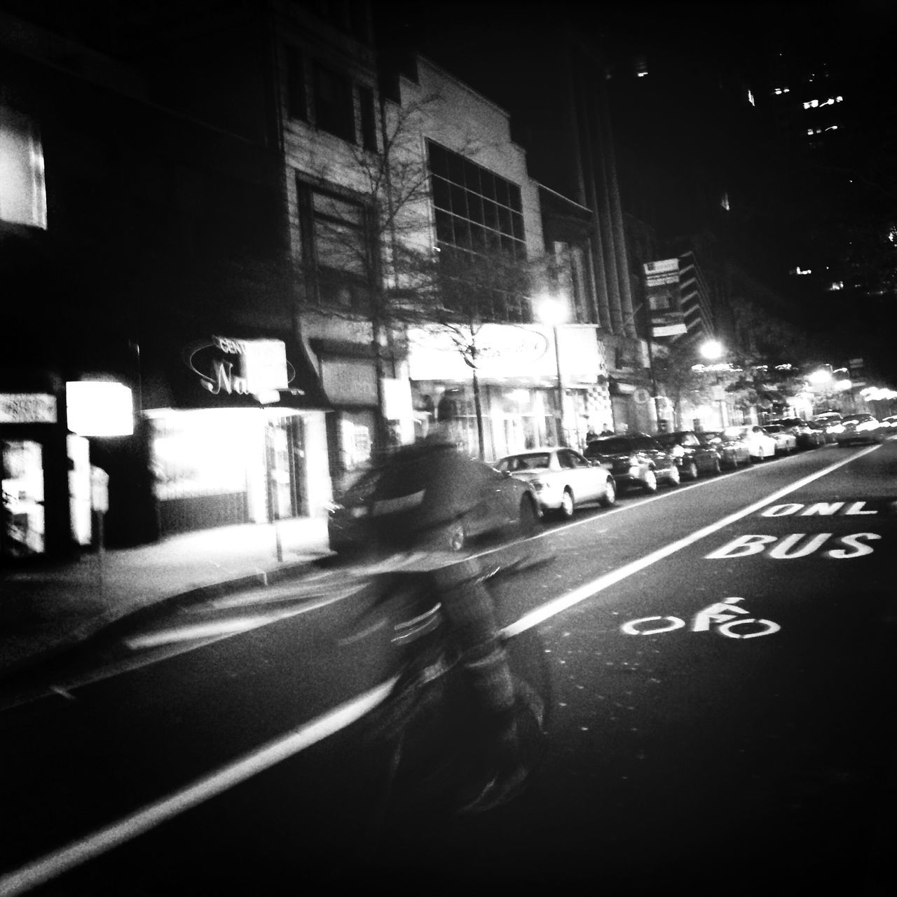 Rear view of a blurred man bicycling on road at night