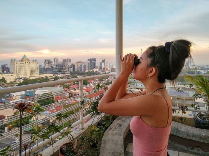 Young woman standing by cityscape against sky in city