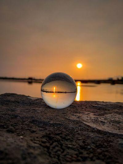 Crystal ball on beach against sky during sunset