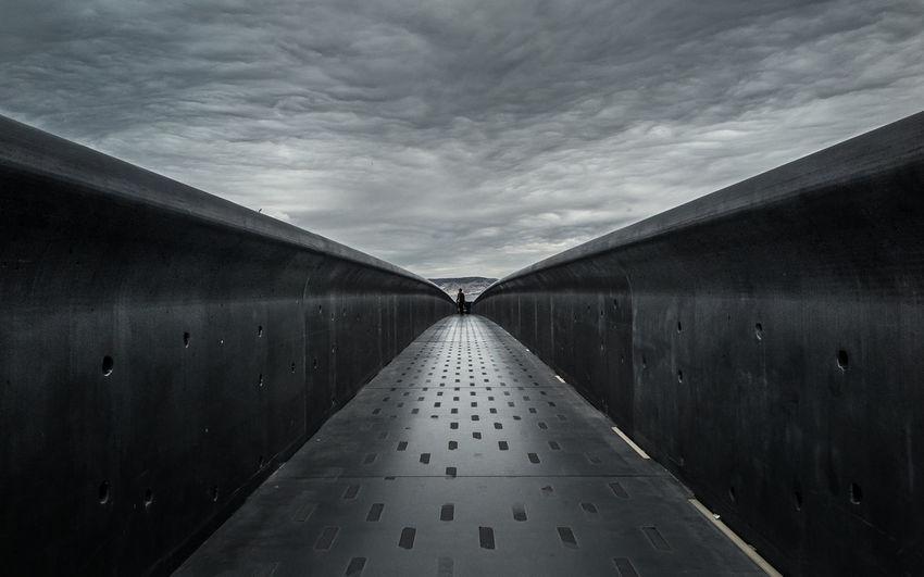 Narrow footbridge under cloudy sky