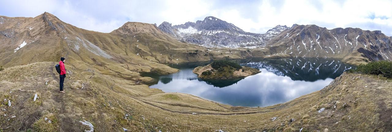 Full length of woman looking at lake against mountain range