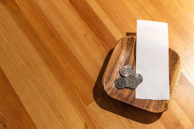 High angle view of coins and paper on table