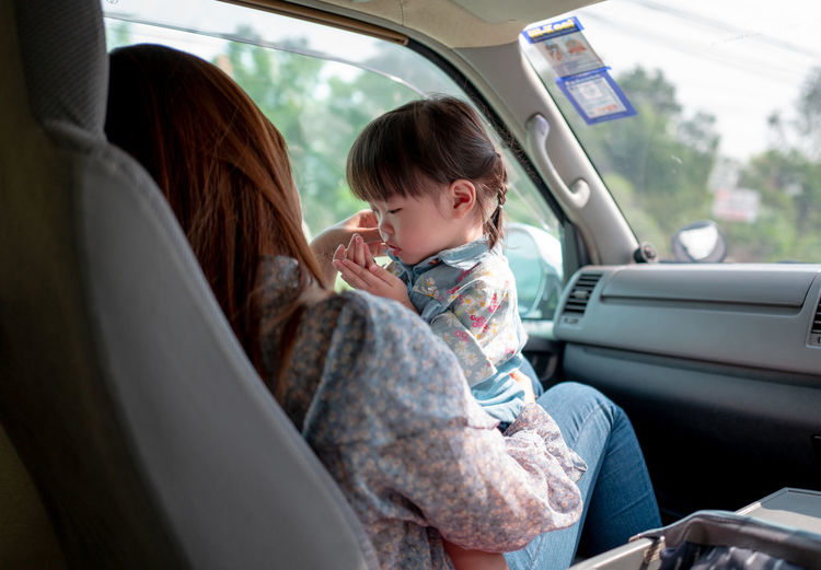 Mother and daughter sitting in car