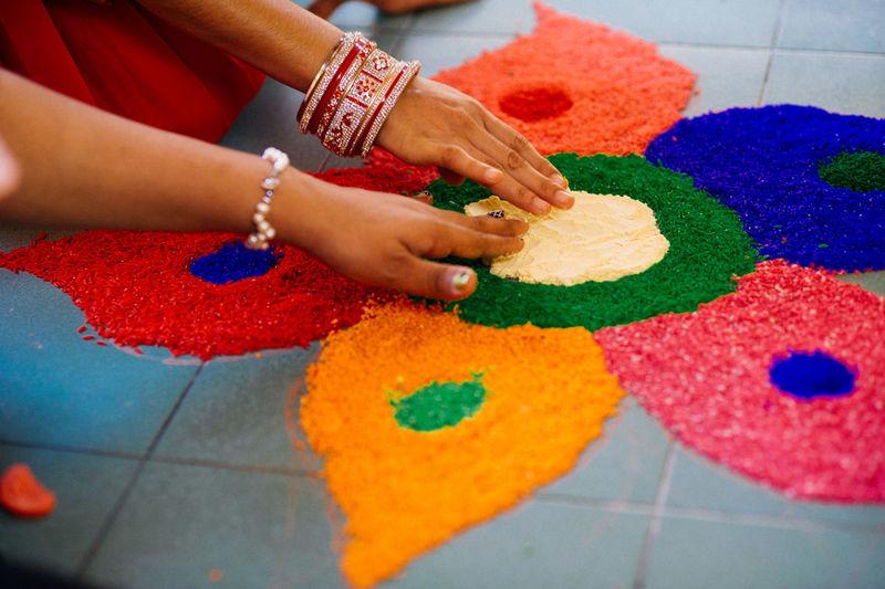 Cropped image of hands making rangoli on tiled floor