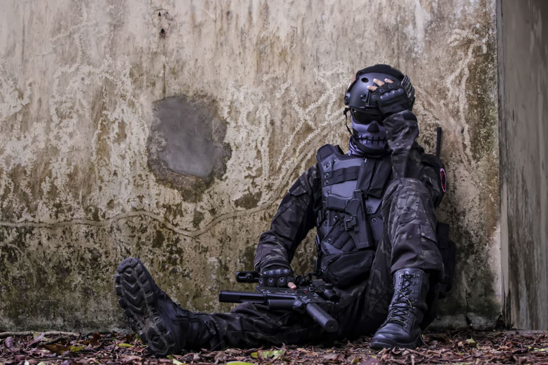 Full length of soldier sitting against old wall in forest