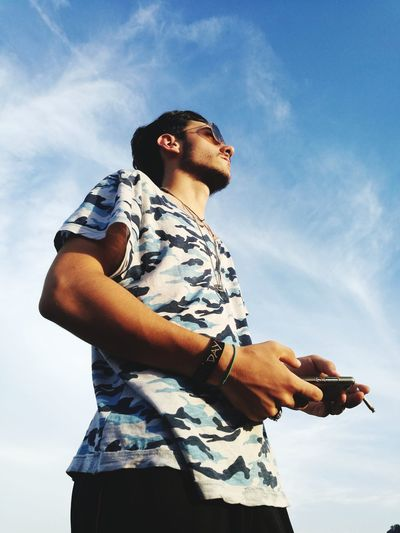 Low angle view of man holding smart phone and cigarette while standing against sky