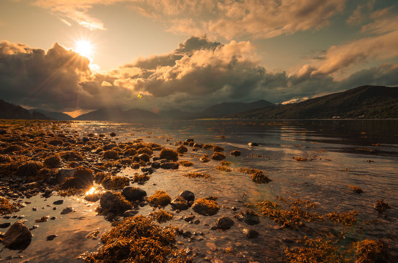 The sun is shining through the clouds on a lake in the scottish highlands