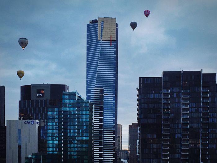 Hot Air Balloons Flying Over Urban Skyline Against Sky