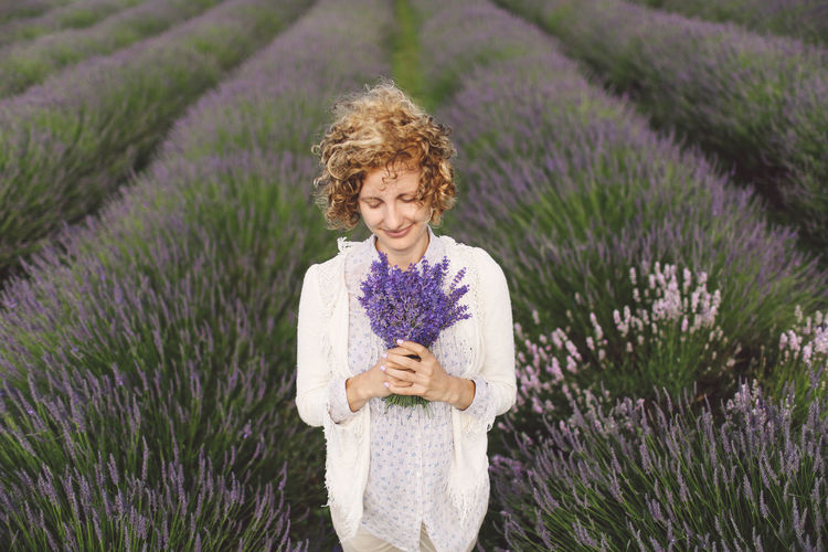 Woman holding lavender flowers on field