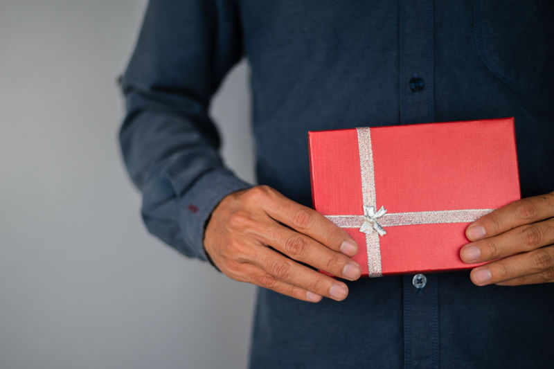 Midsection of man holding red box against white background