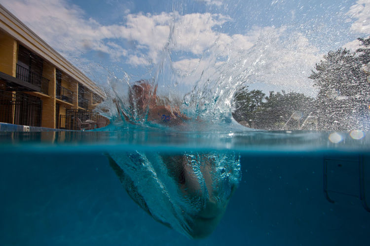 Water splashing in swimming pool against sky