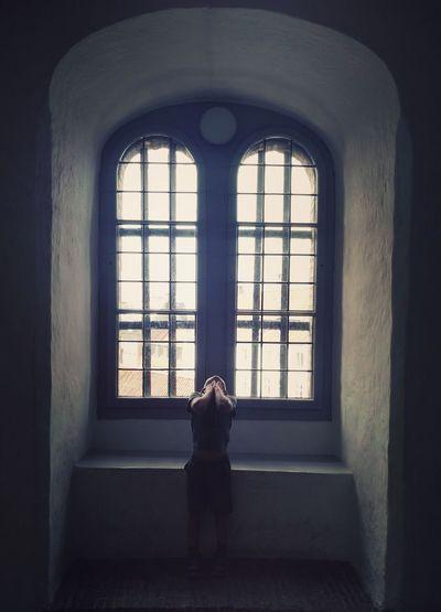 Child Standing Against Window